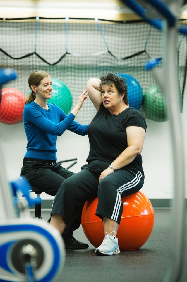 Kristin Campbell guides Scenery Slater through an exercise regiment, part of a study to determine if exercise can counteract chemo-brain. Photo credit: Martin Dee