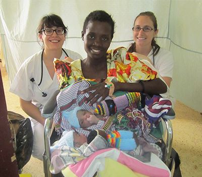 Former UBC Citizens for Global Midwifery Program participants Natalie Amran and Quinn Metcalfe celebrate with a new mother of twins in Uganda in 2012.