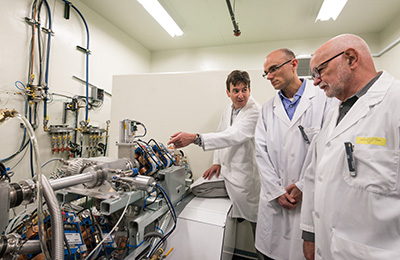 L-R: Francois Benard, Paul Schaffer and Thomas Ruth examine the machinery that directs the proton beam. Photo courtesy of NSERC