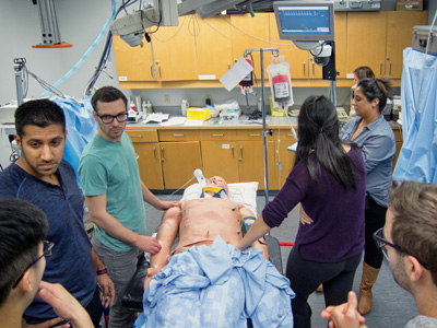 Residents work though a simulated trauma scenario in the POEM course. Photo credit: Brian Kladko