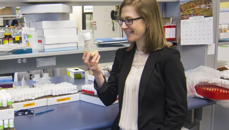 Elizabeth Rideout examines some of her fruit flies. Photo by: Brian Kladko
