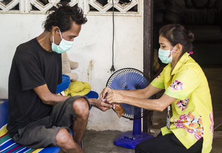 A tuberculosis patient in Thailand receiving therapy during a home visit. Photo: USAID Asia