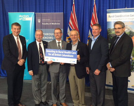 Dean of the Faculty of Medicine Dermot Kelleher (far left) with Minister of Health Terry Lake and founding Rural Health Chair Dave Snadden (holding sign).