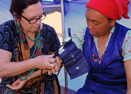 Cathy Ellis (left) provides care in a relief tent after the 2015 earthquake in Nepal.