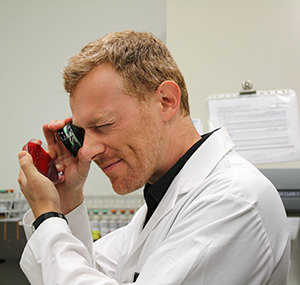 Dr. Marc Romney wears a white lab coat and inspects a sample