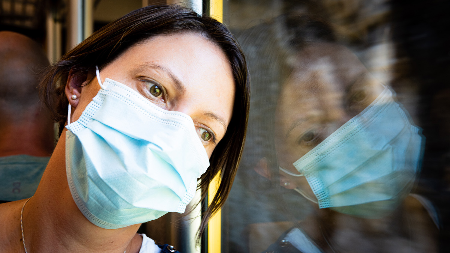 Woman wearing surgical mask leaning her head against window, looking outside